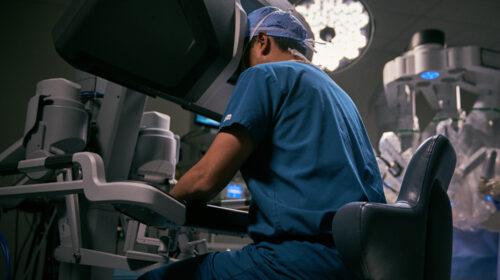 Ein Chirurg sitzt an der Konsole des Da Vinci Roboters von Intuitive Surgical